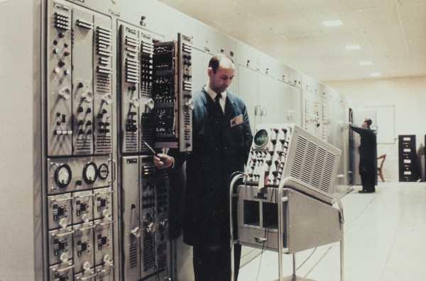 Technician standing beside FST-2 computer - 1985