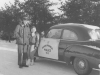 A3C Red Ross and somebody's daughter standing beside an OPPs squad car - January 1953.